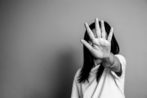 Image of a woman with a hand outstreached covering her face